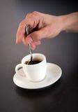 Φλυτζάνι ανακατώματος χεριών του καφέ Espresso με το κουτάλι Στοκ Εικόνες