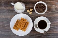 Φλυτζάνι, γάλα κανατών, κύπελλο με τα φασόλια καφέ και τις βιενέζικες βάφλες Στοκ εικόνα με δικαίωμα ελεύθερης χρήσης