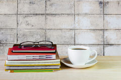 Φλυτζάνι, γυαλιά, και σωρός καφέ του βιβλίου στον ξύλινο πίνακα με τη θαμπάδα Στοκ φωτογραφίες με δικαίωμα ελεύθερης χρήσης