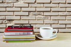 Φλυτζάνι, γυαλιά, και σωρός καφέ του βιβλίου στον ξύλινο πίνακα με τη θαμπάδα Στοκ Φωτογραφίες