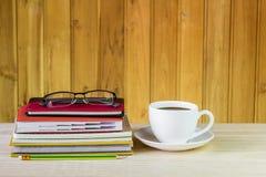 Φλυτζάνι, γυαλιά, και σωρός καφέ του βιβλίου στον ξύλινο πίνακα Στοκ φωτογραφίες με δικαίωμα ελεύθερης χρήσης