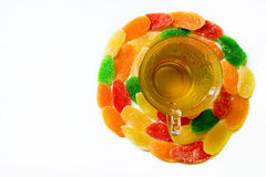 Φλυτζάνι γυαλιού του πράσινου τσαγιού που περιβάλλεται από το γλασαρισμένο ανανά στο λευκό Στοκ Εικόνες
