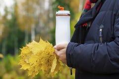 Φλυτζάνι εκμετάλλευσης ατόμων με τα φύλλα ποτών και φθινοπώρου Στοκ Εικόνες