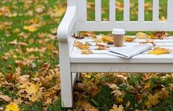 Φλυτζάνι εφημερίδων και καφέ στον πάγκο στο πάρκο φθινοπώρου Στοκ φωτογραφία με δικαίωμα ελεύθερης χρήσης