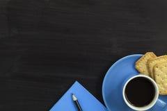Φλυτζάνι και κροτίδες καφέ με το μολύβι σημειωματάριων στο σκοτεινό ξύλο Στοκ εικόνα με δικαίωμα ελεύθερης χρήσης