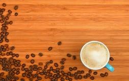 Φλυτζάνι και φασόλια καφέ πέρα από το ξύλινο υπόβαθρο Στοκ Εικόνες