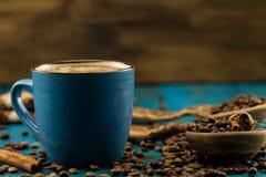 Φλυτζάνι και φασόλια καφέ στο μπλε ξύλινο υπόβαθρο Στοκ Εικόνα