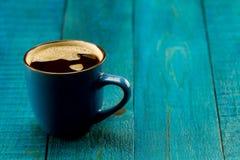 Φλυτζάνι και φασόλια καφέ στο μπλε ξύλινο υπόβαθρο Στοκ φωτογραφία με δικαίωμα ελεύθερης χρήσης