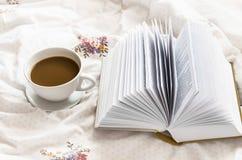 Φλυτζάνι καφέ ακόμα-ζωής και ένα βιβλίο στο κρεβάτι Στοκ Εικόνες