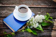 Φλυτζάνι καφέ, βιβλίο και άσπρο ιώδες λουλούδι στο ξύλινο υπόβαθρο Στοκ Εικόνα