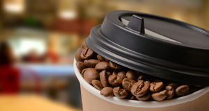 Φλυτζάνι καφέ εγγράφου με το υπόβαθρο φασολιών καφέ Στοκ Φωτογραφίες