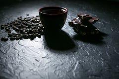 Φλυτζάνι καφέ και φασόλια και σοκολάτα καφέ στο μαύρο υπόβαθρο Στοκ Εικόνες
