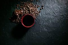 Φλυτζάνι καφέ και φασόλια και σοκολάτα καφέ στο μαύρο υπόβαθρο Στοκ φωτογραφία με δικαίωμα ελεύθερης χρήσης
