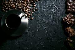 Φλυτζάνι καφέ και φασόλια καφέ στον ξύλινο πίνακα με τα μπισκότα και τη σοκολάτα Στοκ φωτογραφίες με δικαίωμα ελεύθερης χρήσης