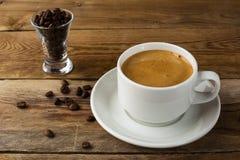 Φλυτζάνι καφέ και φασόλια καφέ στο αγροτικό υπόβαθρο Στοκ εικόνες με δικαίωμα ελεύθερης χρήσης