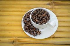 Φλυτζάνι καφέ και φασόλια καφέ στο υπόβαθρο μπαμπού Στοκ εικόνα με δικαίωμα ελεύθερης χρήσης