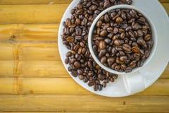 Φλυτζάνι καφέ και φασόλια καφέ στο υπόβαθρο μπαμπού Στοκ Εικόνα