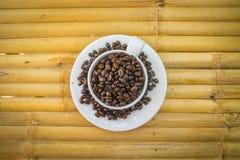 Φλυτζάνι καφέ και φασόλια καφέ στο υπόβαθρο μπαμπού Στοκ Εικόνες