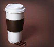 Φλυτζάνι καφέ με τα φασόλια καφέ στο καφετί υπόβαθρο. Take-$l*away Στοκ φωτογραφία με δικαίωμα ελεύθερης χρήσης