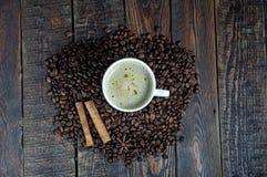 Φλυτζάνι καφέ με το αστέρι ραβδιών κανέλας και anis στον παλαιό αγροτικό πίνακα Τοπ όψη Στοκ Εικόνες