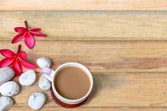 Φλυτζάνι καφέ με το λουλούδι Plumeria και πέτρα στο ξύλινο πιάτο Στοκ Εικόνες