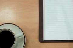 Φλυτζάνι καφέ με το σημειωματάριο πέρα από τον ξύλινο πίνακα έτοιμος για το mockupe Στοκ φωτογραφίες με δικαίωμα ελεύθερης χρήσης