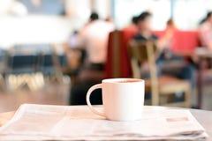 Φλυτζάνι καφέ πέρα από την εφημερίδα στον πίνακα στη καφετερία στοκ εικόνα