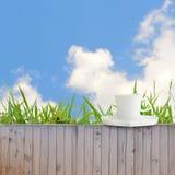 Φλυτζάνι καφέ που τίθεται στο φράκτη ως σύσταση υποβάθρου μπλε ουρανού και σύννεφων Στοκ εικόνες με δικαίωμα ελεύθερης χρήσης