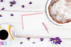 Φλυτζάνι καφέ, σπιτικά κέικ και έγγραφο για ένα άσπρο αγροτικό ξύλινο υπόβαθρο Στοκ φωτογραφία με δικαίωμα ελεύθερης χρήσης