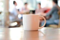 Φλυτζάνι καφέ στον πίνακα με τους ανθρώπους στη καφετερία ως υπόβαθρο θαμπάδων στοκ φωτογραφίες