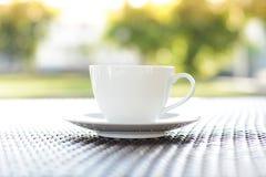 Φλυτζάνι καφέ στον πίνακα με το θολωμένο πράσινο υπόβαθρο φύσης στοκ φωτογραφία με δικαίωμα ελεύθερης χρήσης
