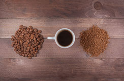 Φλυτζάνι μεταξύ των χουφτών των φασολιών και του στιγμιαίου καφέ Στοκ Εικόνα