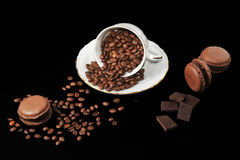 Φλυτζάνι με τα φασόλια καφέ και το κέικ σοκολάτας macarons και κομμάτια του CH Στοκ Εικόνα