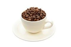 Φλυτζάνι με τα φασόλια καφέ σε ένα πιατάκι Στοκ φωτογραφία με δικαίωμα ελεύθερης χρήσης