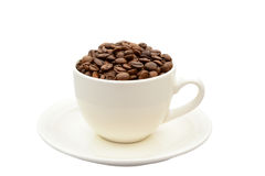 Φλυτζάνι με τα φασόλια καφέ σε ένα πιατάκι Στοκ εικόνα με δικαίωμα ελεύθερης χρήσης