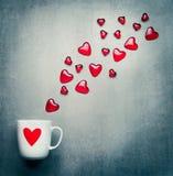 Φλυτζάνι με την κόκκινη καρδιά και τις πετώντας καρδιές γυαλιού Ρομαντικά σύμβολα αγάπης, ημέρα βαλεντίνων ή έννοια γενεθλίων Στοκ Φωτογραφίες
