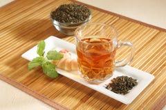 Φλυτζάνι με το πράσινα τσάι και τα φύλλα Στοκ Εικόνες