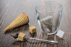 Φλυτζάνι με teabag, κώνοι γκοφρετών με τη σοκολάτα που γεμίζεται, καφετιά ζάχαρη Στοκ φωτογραφία με δικαίωμα ελεύθερης χρήσης