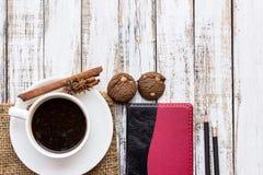 Φλυτζάνι, μπισκότο, καρυκεύματα και σημειωματάριο καφέ στον ξύλινο πίνακα στοκ εικόνες