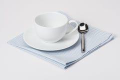 Φλυτζάνι, πιάτο και κουτάλι στο διπλωμένο Gingham βαμβάκι Στοκ Εικόνα