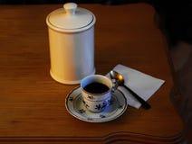 Φλυτζάνι πορσελάνης με τον καφέ και ένα ασημένιο κουτάλι Στοκ Φωτογραφία