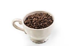 Φλυτζάνι που γεμίζουν με τα φασόλια καφέ που απομονώνονται στο λευκό Στοκ Εικόνα