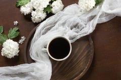 Φλυτζάνι πρωινού του μαύρου καφέ με το ντεκόρ των λουλουδιών του viburnum επάνω από την όψη Στοκ Εικόνες