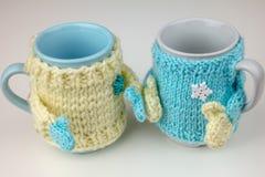 Φλυτζάνι στο πλεκτό πουλόβερ με τα χέρια στοκ εικόνες
