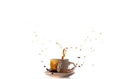 Φλυτζάνι της ανατροπής του μαύρου καφέ που δημιουργεί έναν παφλασμό Στοκ Φωτογραφία