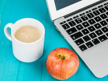 Φλυτζάνι της σούπας μανιταριών με έναν φορητό προσωπικό υπολογιστή και την κόκκινη Apple Στοκ Φωτογραφία