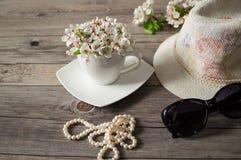 Φλυτζάνι του ανθίζοντας δέντρου αχλαδιών λουλουδιών, γυαλιά ηλίου, ψάθινο καπέλο Στοκ Φωτογραφίες