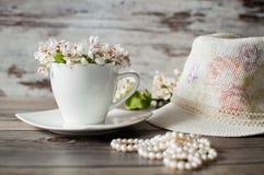 Φλυτζάνι του ανθίζοντας δέντρου αχλαδιών λουλουδιών, χάντρες από τα μαργαριτάρια Στοκ Εικόνες
