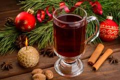 Φλυτζάνι του θερμαμένων κρασιού, του κεριού και της σφαίρας Χριστουγέννων Στοκ Εικόνα