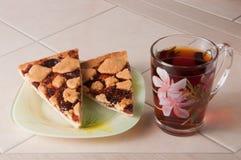 Φλυτζάνι του κέικ τσαγιού και δαμάσκηνων με το ψίχουλο σε χαρτί περγαμηνής Στοκ φωτογραφία με δικαίωμα ελεύθερης χρήσης